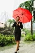 Business woman using mobile phone, holding umbrella - Alex Microstock02