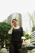 Business woman using mobile phone, low angle view, buildings in the background - Alex Microstock02