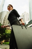 Business woman walking with briefcase, buildings in the background - Alex Microstock02