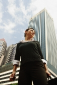 Business woman standing, looking away, buildings in the background - Alex Microstock02