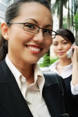 Business woman, smiling, looking at camera, woman in the background on the phone - Alex Microstock02