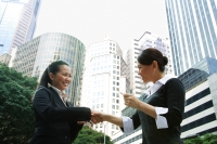 Two business women shaking hands, one holding business card, low angle view - Alex Microstock02