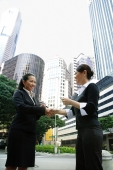 Two business women shaking hands, one holding business card - Alex Microstock02