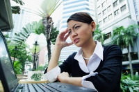 Business woman using laptop, frowning, hand on head - Alex Microstock02