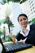 Business woman with laptop, holding coffee cup, smiling at camera - Alex Microstock02