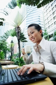 Business woman using laptop, holding coffee cup - Alex Microstock02