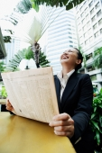 Business woman holding newspaper, looking up - Alex Microstock02
