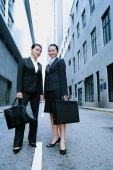 Business women standing side by side looking at camera - Alex Microstock02