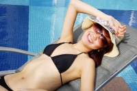 Young woman in bikini, wearing hat and sunglasses, lounging by pool, looking at camera - Alex Microstock02