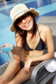 Young woman in bikini, wearing hat and sunglasses, holding cocktail glass, looking at camera - Alex Microstock02