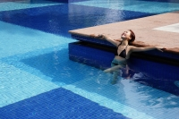 Young woman in swimming pool, leaning on edge of pool - Alex Microstock02