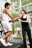 Couple in gym, man walking on treadmill, woman standing next to him - Alex Microstock02