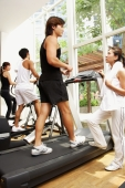Young adults in gym, walking on treadmill - Alex Microstock02