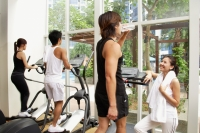 Young adults in gym, walking on treadmill, man drinking water - Alex Microstock02