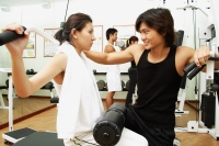 Couple working out in gym, weight training, people in the background - Alex Microstock02