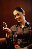 Young woman with champagne glass, using mobile phone, text messaging - Alex Microstock02