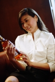 Woman holding and looking at alcohol bottle - Alex Microstock02