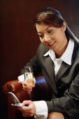 Woman holding glass of champagne and mobile phone, text messaging - Alex Microstock02