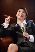 Businesswoman holding glass of champagne and cigar, looking up - Alex Microstock02