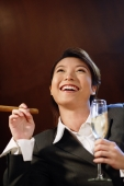 Businesswoman with glass of champagne and cigar, looking up, - Alex Microstock02