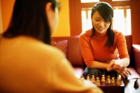 Young women sitting, playing chess - Alex Microstock02