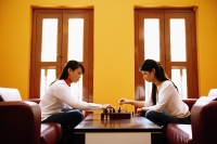 Young women sitting in living room, playing chess - Alex Microstock02