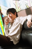 Young man sitting on sofa, using mobile phone - Alex Microstock02