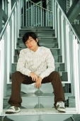 Young man sitting on steps, looking at camera - Alex Microstock02