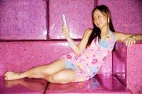 Young woman, lying on sofa, holding mobile phone - Alex Microstock02