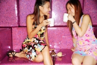 Young women sitting on sofa, drinking from mugs - Alex Microstock02
