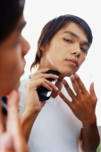 Young man looking at mirror, shaving with electric shaver - Alex Microstock02