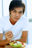 Young man looking at camera, bowl of salad in front of him - Alex Microstock02
