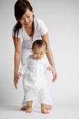 Baby girl standing, mother behind her - Alex Microstock02