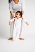 Baby boy standing, mother behind him holding his arms - Alex Microstock02