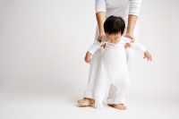 Baby boy standing, being supported by mother from behind - Alex Microstock02