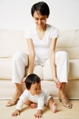 Mother sitting on sofa, baby boy sitting on floor - Alex Microstock02