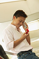 Man looking at ring box, using mobile phone, smiling - Alex Microstock02