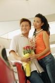Couple standing, man holding bouquet, woman holding wine glass - Alex Microstock02