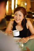 Couple in cafe, woman holding cup, looking at man across from her - Alex Microstock02