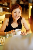Couple in cafe, woman holding cup, over the shoulder view - Alex Microstock02