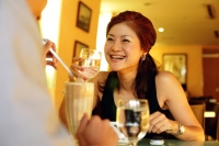 Couple in restaurant, woman holding glass and smiling - Alex Microstock02