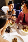 Friends in restaurant raising wine glasses for a toast - Alex Microstock02