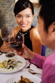 Couple in restaurant holding wine glasses for a toast - Alex Microstock02