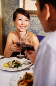 Couple in restaurant toasting with wine glasses - Alex Microstock02