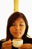 Young woman holding cup of coffee, eyes closed - Alex Microstock02