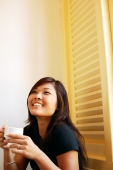 Young woman holding cup of coffee, looking up, smiling - Alex Microstock02
