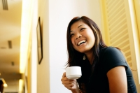 Young woman holding cup of coffee, looking away, smiling - Alex Microstock02