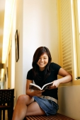 Young woman sitting, reading a book, smiling - Alex Microstock02