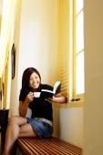 Young woman sitting, reading a book and holding cup of coffee - Alex Microstock02