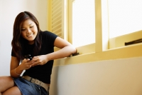 Young woman sitting next to window, looking at mobile phone - Alex Microstock02